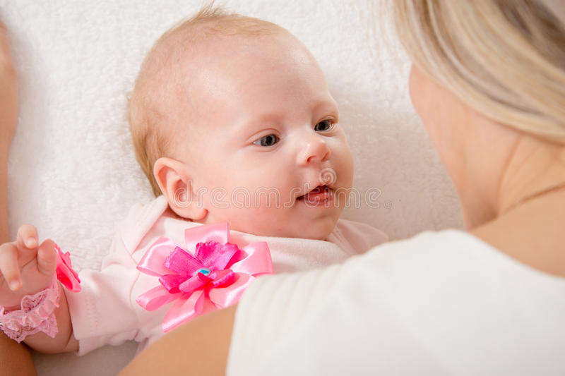 The two-month baby looking at mother. A two-month baby lying on his back on the bed, sitting next to the child and mother looking at her royalty free stock photography