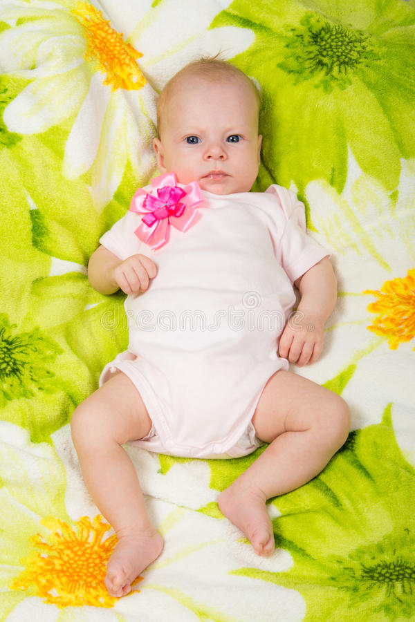 The two-month baby lying on the bed on his back looking at the frame. A two-month baby girl lying on the bed Europeans on colored coverlet stock photos