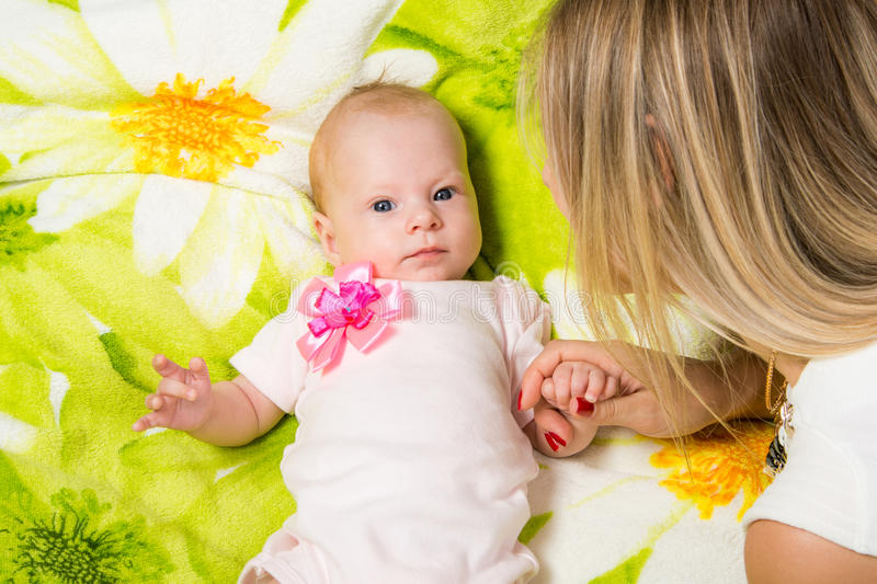 The two-month baby lying on the bed, sitting next to mom. A two-month baby lying on his back on the bed, sitting next to the mother and the baby looks at her royalty free stock images