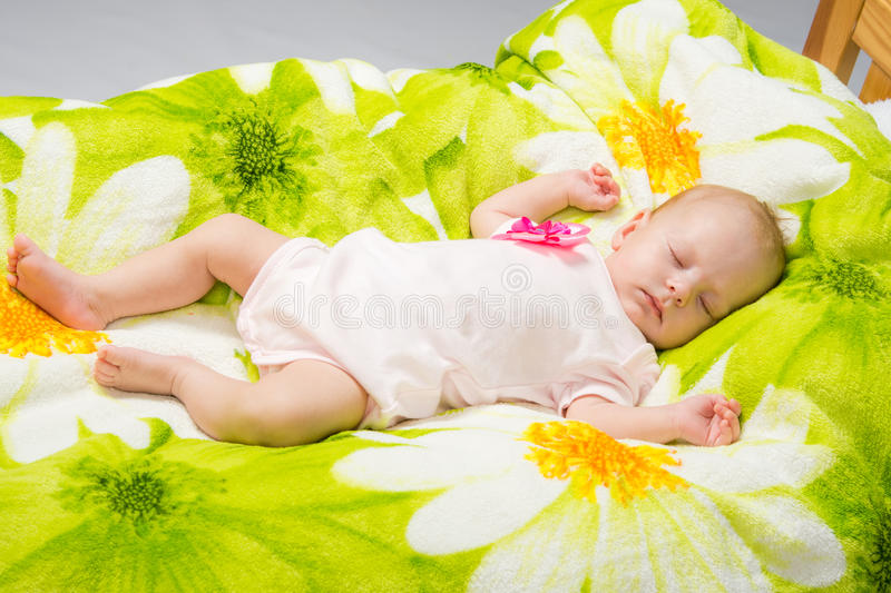 The two-month baby sleeps happily in bed. A two-month baby girl Europeans lies on a soft bed on colored coverlet royalty free stock photography
