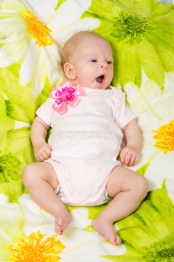 The two-month baby yawns lying on his back on the bed. A two-month baby girl lying on the bed Europeans on colored coverlet royalty free stock photo