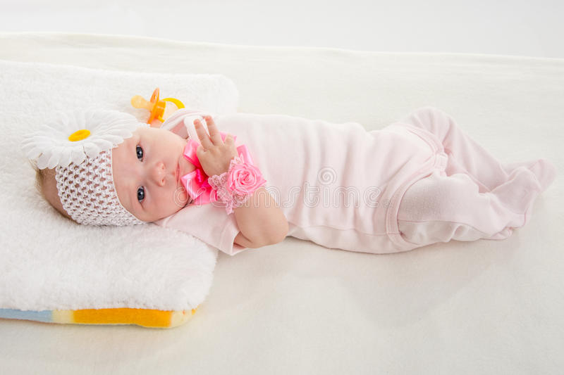 The two-month girl lying on the bed. A two-month baby girl Europeans on the back with a bandage on his head with a flower lying on a soft bed royalty free stock photo