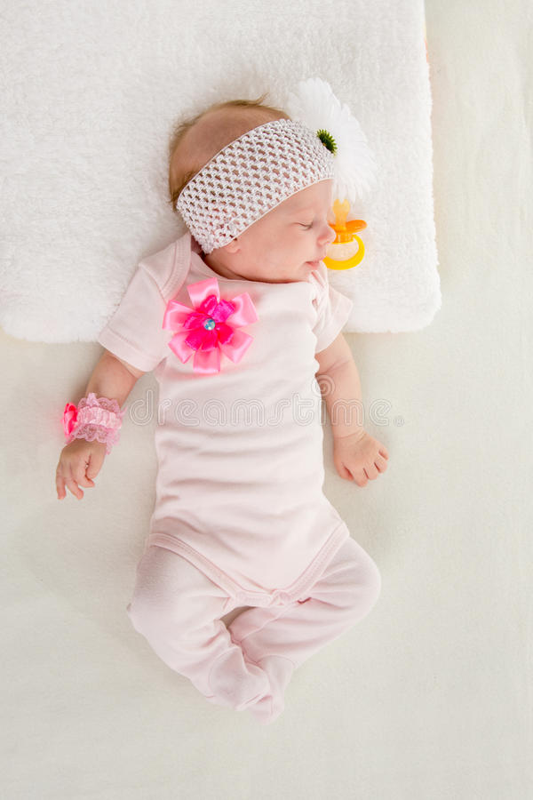 The two-month girl sleeping on the bed. A two-month baby girl Europeans lies on his back with a bandage on his head with a flower royalty free stock photo