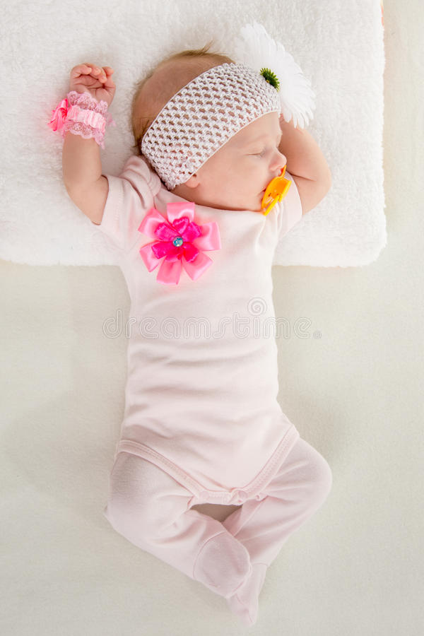 The two-month girl sleeps on the bed at the head outstretched hands. A two-month baby girl Europeans lies on his back with a bandage on his head with a flower royalty free stock photography
