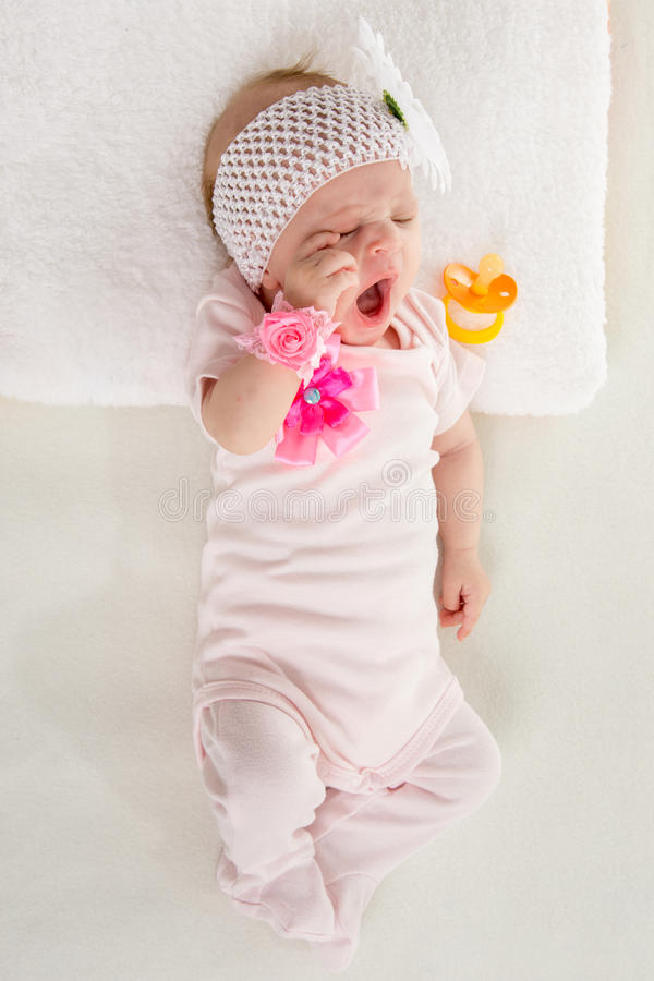 The two-month girl waking up in bed yawning. A two-month baby girl Europeans lies on his back with a bandage on his head with a flower stock photography