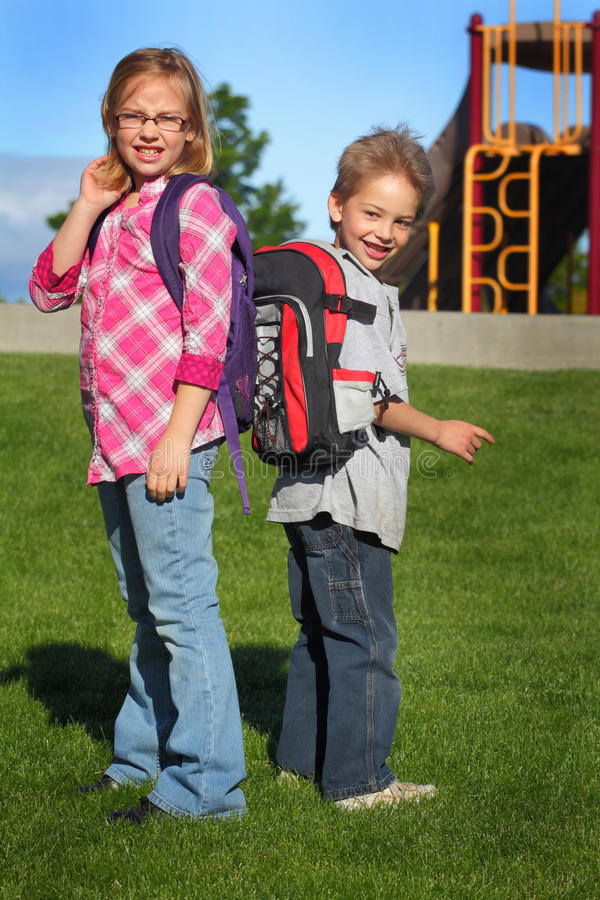 Two Morning School Kids. An early morning shot of two typical elementary school kids with backpacks stock image