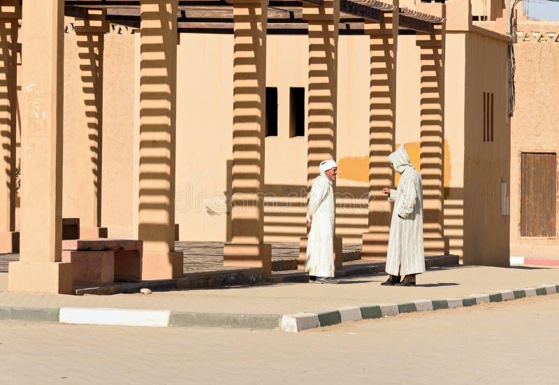 Two Moroccan men in white djellaba talk on the street in Merzouga village, Morocco stock photos
