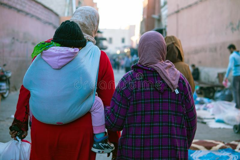Two moroccan women with child in sling seen from the back dressed in typical blue and brown djellaba walk down the. Streets of Marrakesh Medina, Morocco stock image