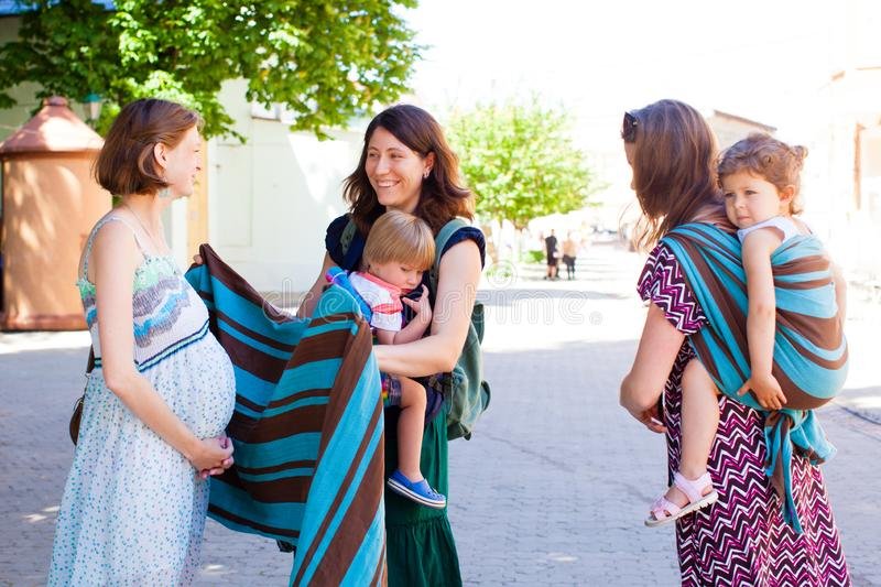 Two mothers giving advices to their pregnant friend stock images