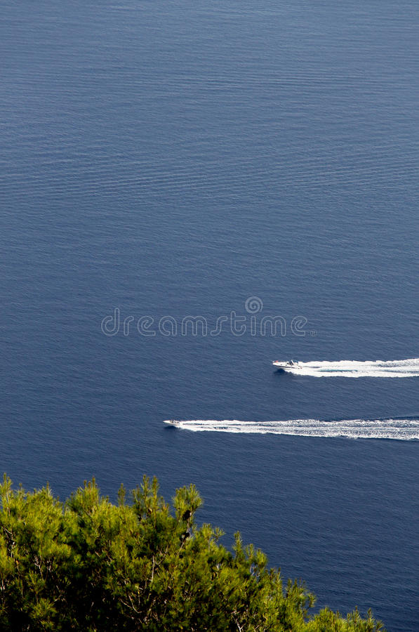 Two motorboats against a blue sea and trees stock photography