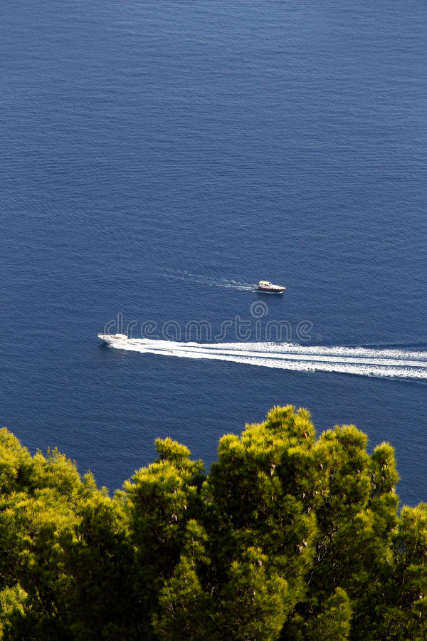 Two motorboats against a blue sea and trees stock photo