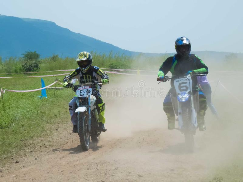 Motorcycle rider overtaking in motocross event. Two motorcycle rider in motocross event on dust track trying to overtake each other. Event takes place in India royalty free stock photos