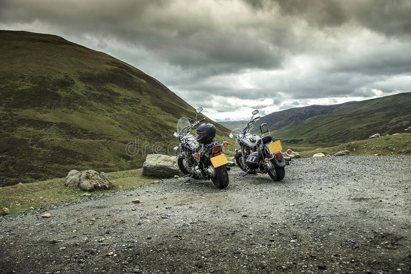 Two motorcycles under hills. Cairngorm Mountains. Braemar, Aberdeenshire, Scotland, United Kingdom. Two motorcycles under hills near Old Military Road royalty free stock photo
