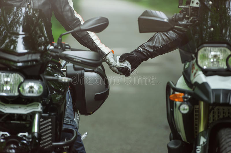 Two motorcyclists are holding hands while sitting on motorcycles royalty free stock photos