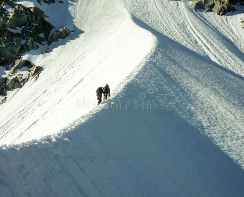 Mountain climbers on narrow snow ridge on a steep climbing route in the French Alps in Chamonix. Two mountain climbers on narrow snow ridge on a steep climbing royalty free stock photos