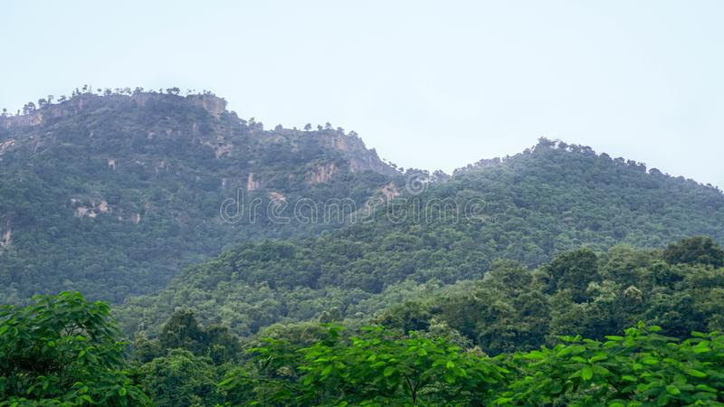 Two mountain peaks with forest at the base at Maharashtra, India. These two mountain peaks look like the Rocky Mountains of Khandala and Lonavala in Maharashtra stock photos