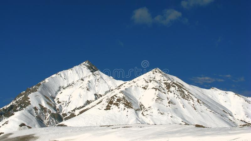 Two mountain peaks. Covered with snow stock images