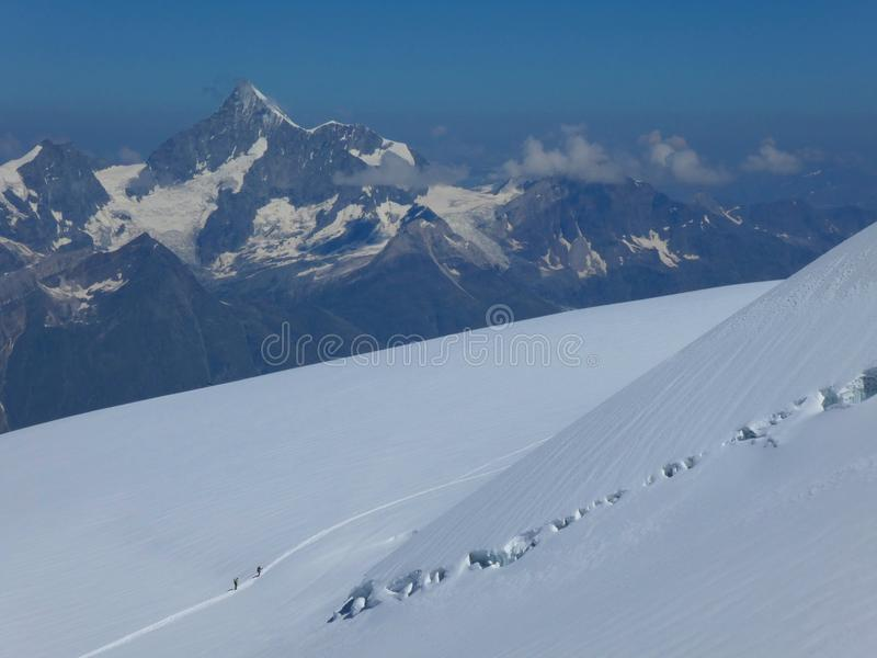 Two mountaineers summiting Monte Rosa on a glacier royalty free stock photo