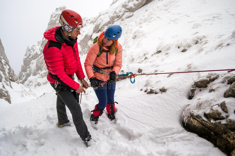 Two mountaineers discussing safety abseiling procedures before rappeling down a snowy chutte, on a difficult Winter route royalty free stock photo