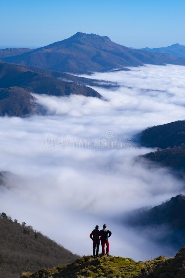 Two mountaineers with sea of clouds and Mount Larun in the background from the natural park of Aiako Harriak, Euskadi Pyrenees stock image