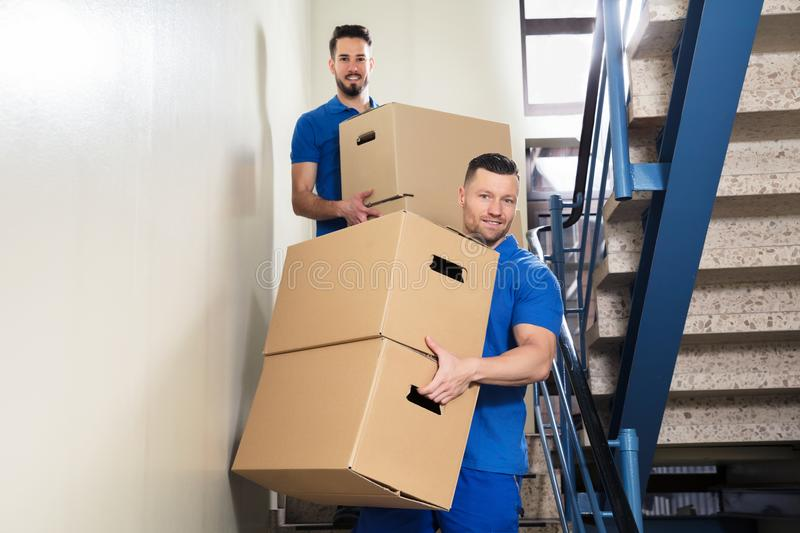 Two Movers Carrying Cardboard Boxes On Staircase royalty free stock image