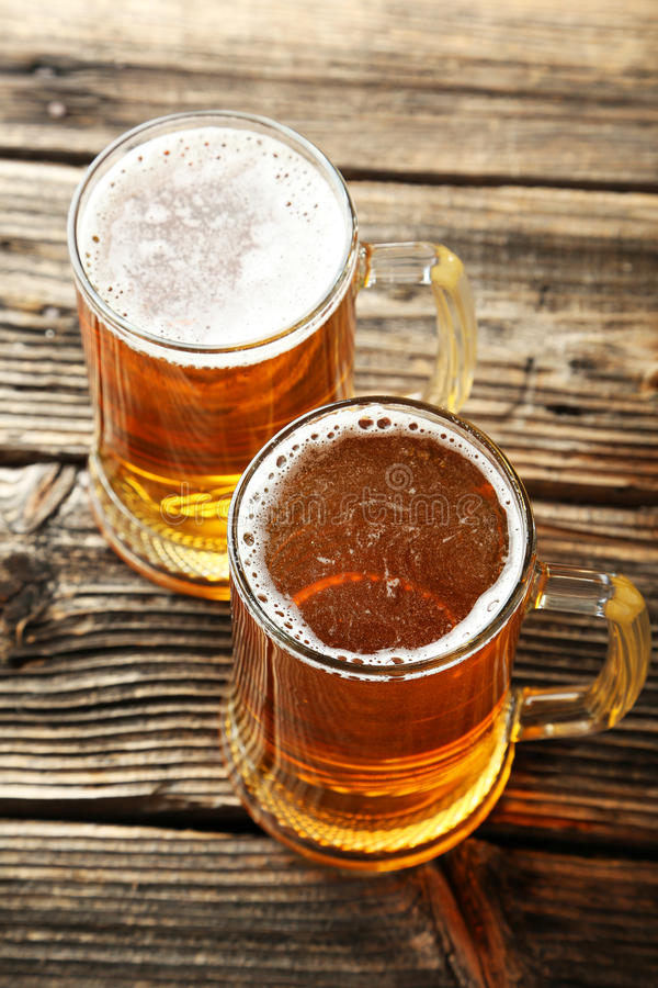 Two mug of beer on brown wooden background. stock image