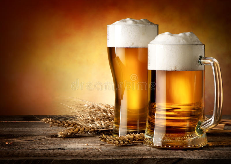 Two mugs of beer. And wheat on a wooden table