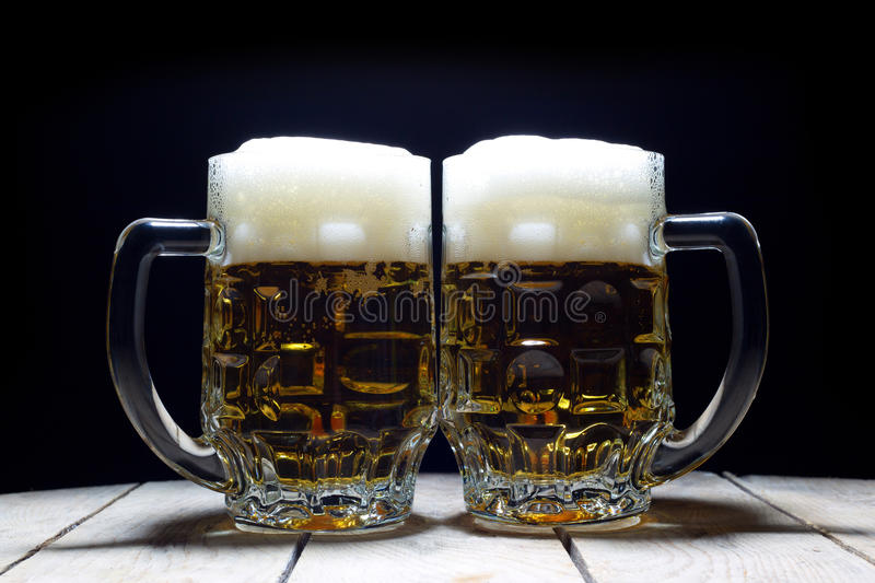 Two Mugs of Cold Beer Are the Best Way to Quench Thirst. On Black Background royalty free stock image