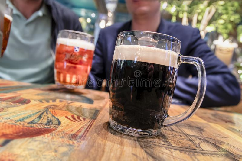 Two mugs of dark and light beer on vintage tavern table. Concept of a friendly feast, a fun meeting. Two mugs of dark and light beer on vintage tavern table royalty free stock image