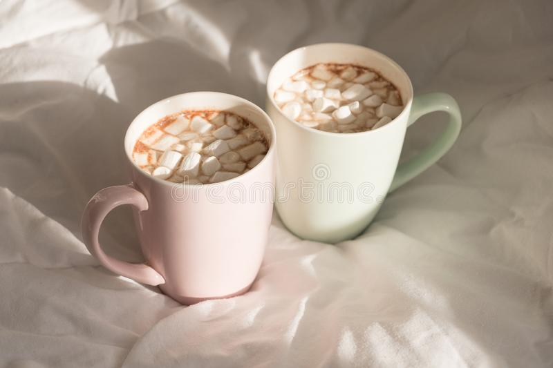 Two mugs of hot chocolate with marshmallows on the bed. Good morning, world. Two mugs of hot chocolate with marshmallows on the bed. Good morning, world royalty free stock photo