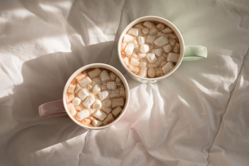Two mugs of hot chocolate with marshmallows on the bed. Good morning, world.  royalty free stock image