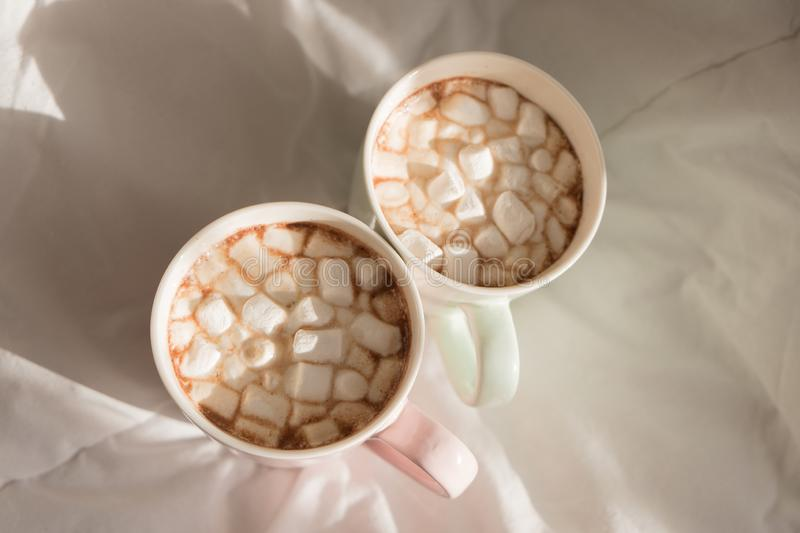 Two mugs of hot chocolate with marshmallows on the bed. Good morning, world. Two mugs of hot chocolate with marshmallows on the bed. Good morning, world stock image
