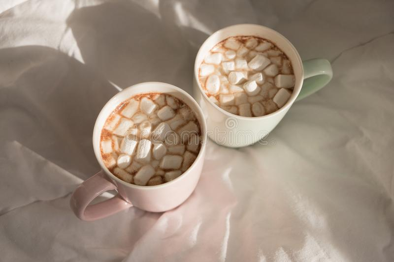 Two mugs of hot chocolate with marshmallows on the bed. Good morning, world. Two mugs of hot chocolate with marshmallows on the bed. Good morning, world stock images