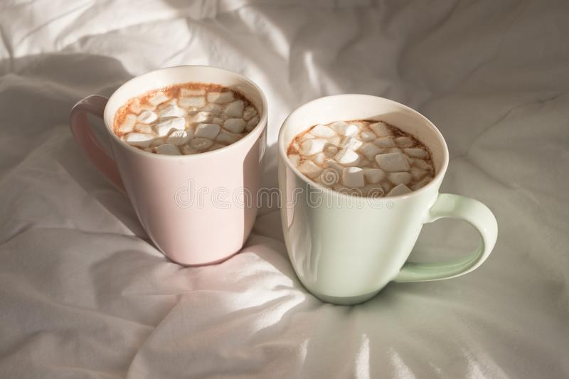 Two mugs of hot chocolate with marshmallows on the bed. Good morning, world.  stock images