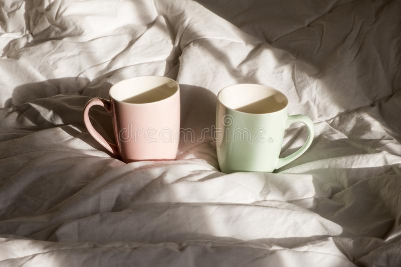 Two mugs of hot chocolate with marshmallows on the bed. Good morning, world. Two mugs of hot chocolate with marshmallows on the bed. Good morning, world royalty free stock images