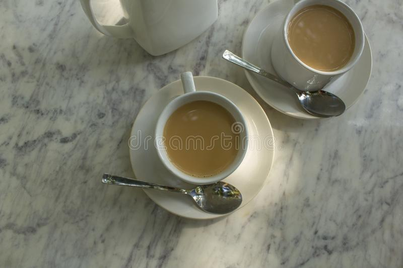 Two mugs with milk drink on plates with spoons near the ceramic teapot on the white marble table close-up top view stock image
