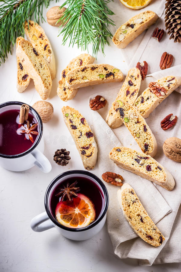 Two mugs of mulled wine and italian biscotti cookies on wooden table.Style rustic. stock photos