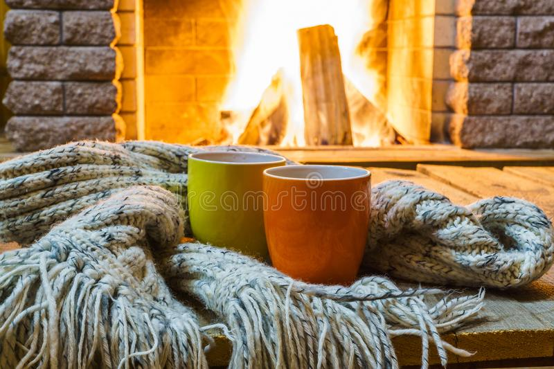 Two mugs for tea or coffee before fireplace. Two mugs for tea or coffee, woolen things near cozy fireplace, in country house, winter vacation, horizontal royalty free stock photography