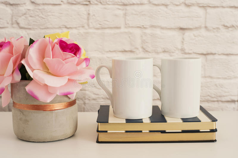 Two Mugs. White Mugs Mockup. Blank White Coffee Mug Mock Up. Styled Photography. Coffee Cup Product Display. Two Coffee Mugs On St. Riped Design Notebooks. Vase royalty free stock image