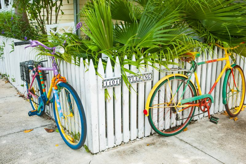 Two multi-colored cycles attached to white picket fence as street art stock image