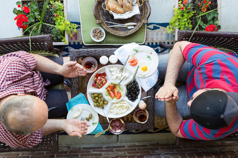 Two multi denominational men praying over food stock photography
