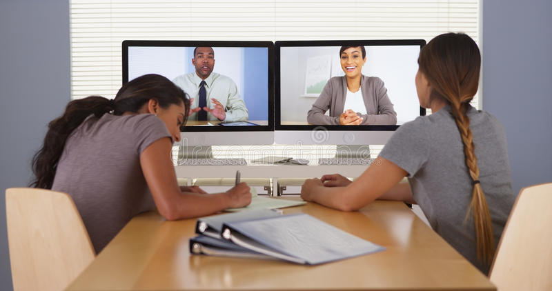 Two multi-ethnic businesswomen talking with tablet at desk stock images