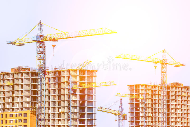 Two multi-storey buildings under construction. Many cranes. Construction of modern housing. Building bussiness. Sun rays and glare stock photography