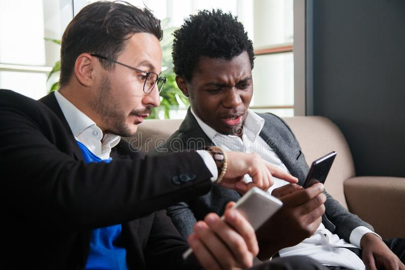 Two multicultural men sit on sofa, smile and hold mobile phones stock photography