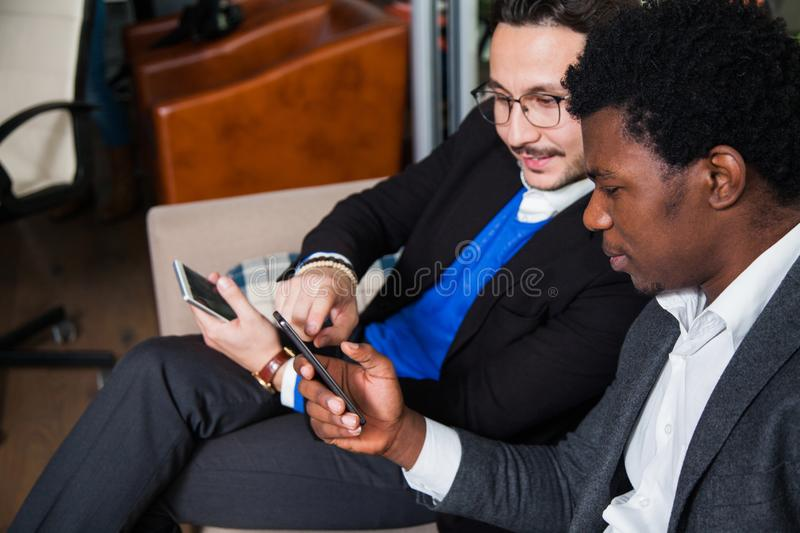 Two multicultural men sit on sofa, smile and hold mobile phones royalty free stock photos