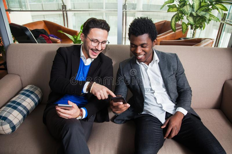 Two multicultural men sit on sofa, smile and hold mobile phones stock photos