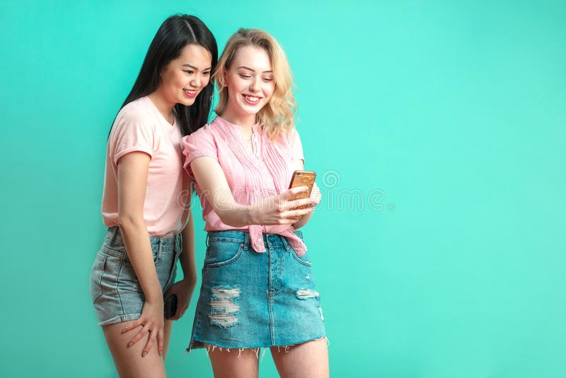 Two multiethnic beautiful women asian and caucasian taking selfie at studio stock photography