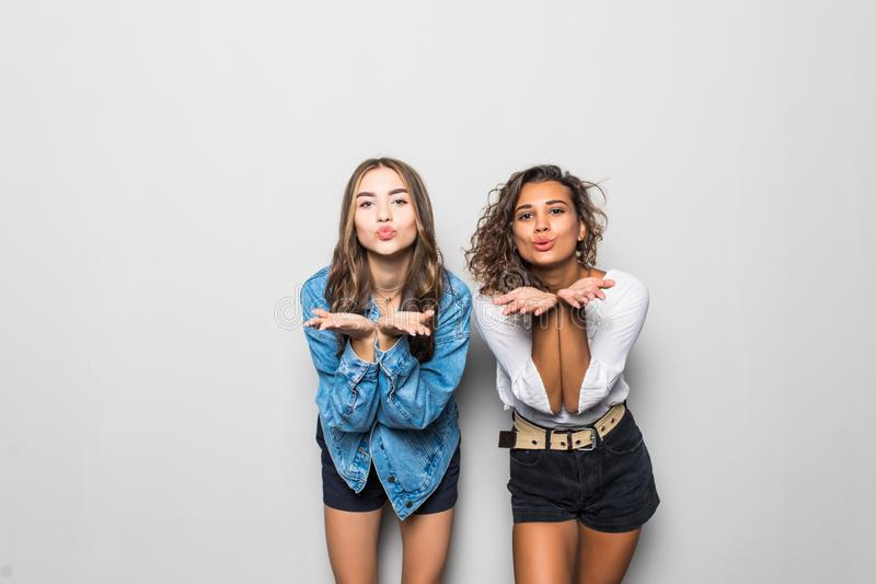 Two multiethnic girls blow airkiss at camera, wears trendy shades, summer clothing, express love or say goodbye on distance, pose. Two multiethnic sisters blow royalty free stock images
