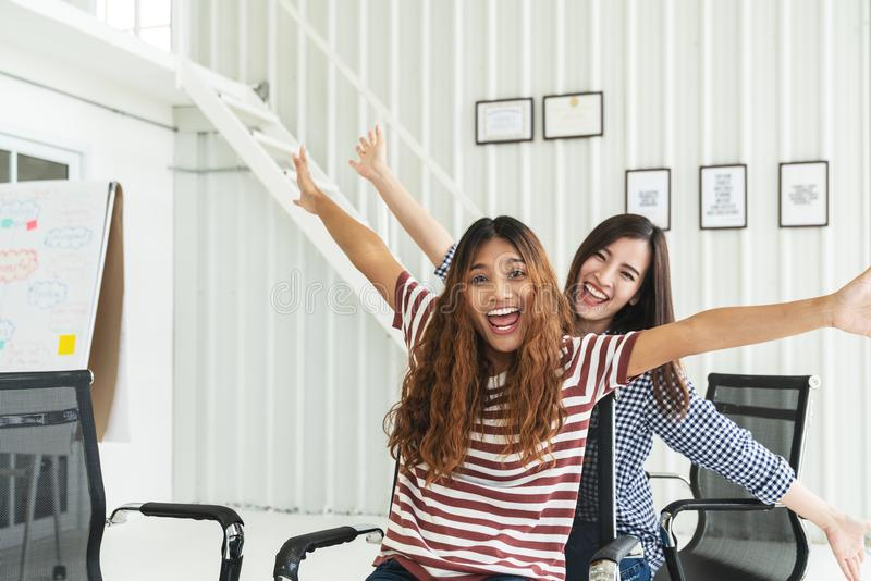 Two multiethnic young creative teamwork having fun laughing, smiling and sitting in office chairs. Coworker women celebrating for royalty free stock image