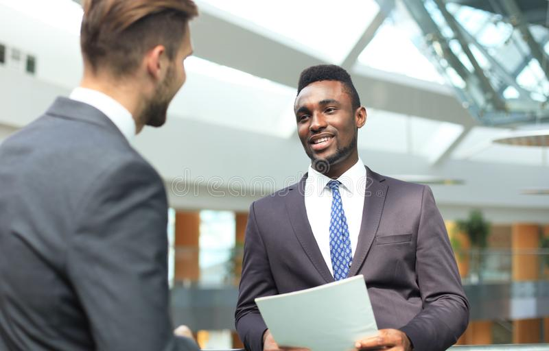 Two multinational young businessmen discussing business at meeting in office. royalty free stock photography